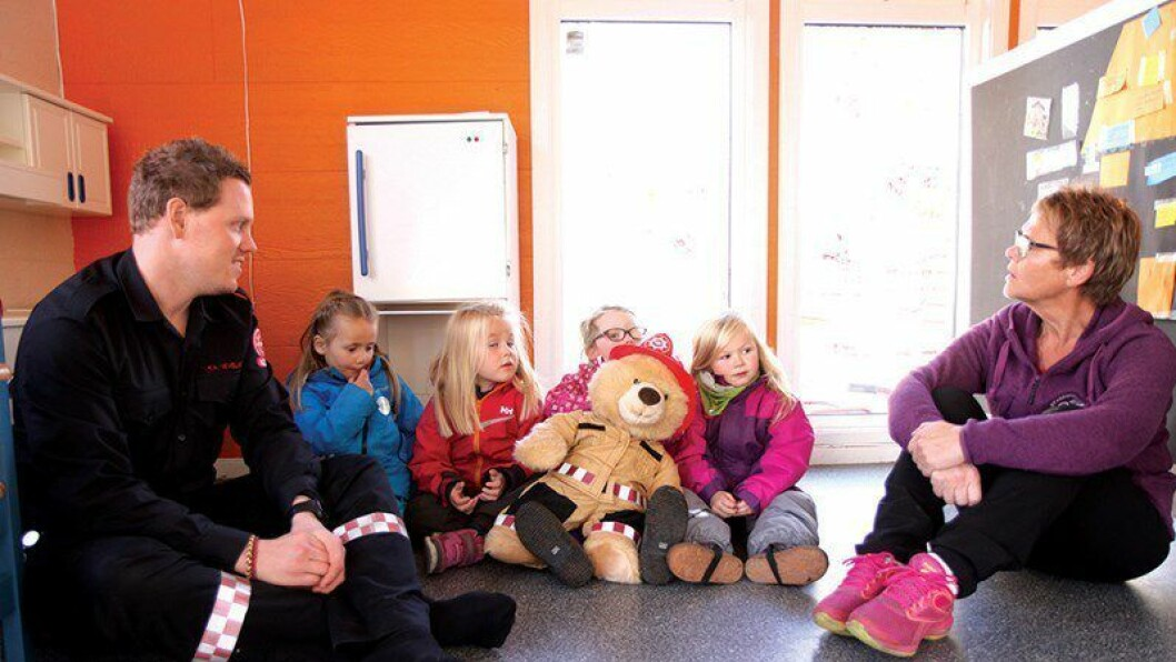 Brannsikkerhet: Branningeniør Ken A. Vevelstad i Kristiansandregionen Brann og Redning får hjelp av bamsen Flammbært og Emma (4), Erle (4), Anna (5) og Catharna (5) i Stasjonshaven barnehage til å sjekke sikkerheten hjemme — og gjerne også hos besteforeldre. Assistent og brannvernleder Sissel Myran synes prosjektet er positivt.