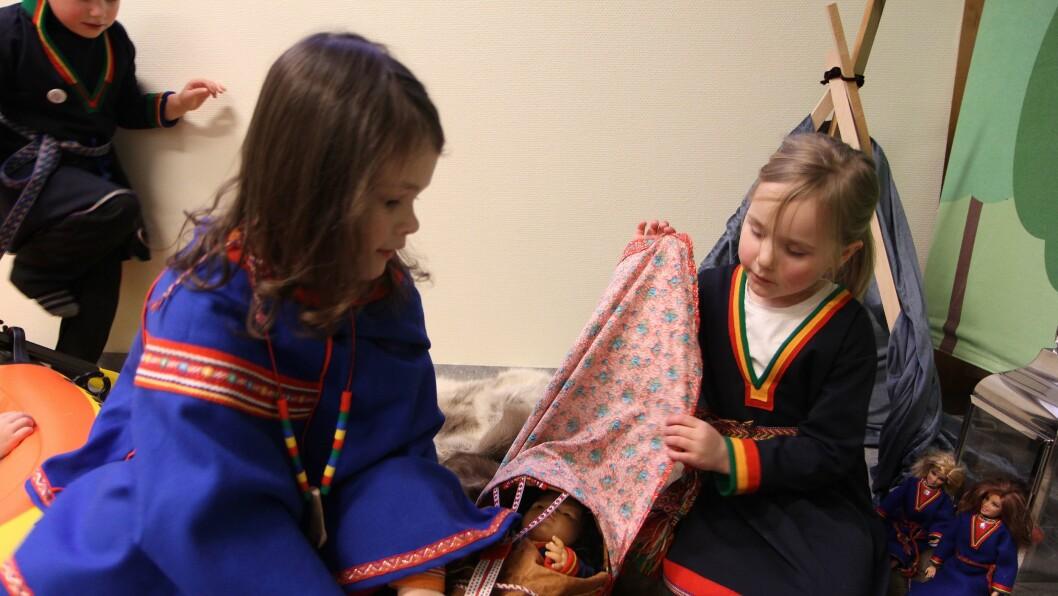 Gabriella (5) og Hannah (5) passer på at den lille samedukka holder bena varme. Den provisoriske sameleiren brukes til samlingsstunder og eventyr. Samiske Barbie en og to får se på.