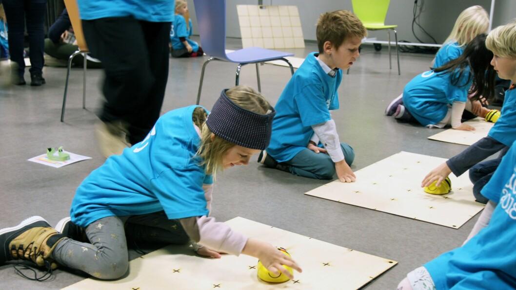 Ved å trykke på ulike knapper på bie-roboten kan barna få roboten til å bevege seg i den retningen de ønsker.