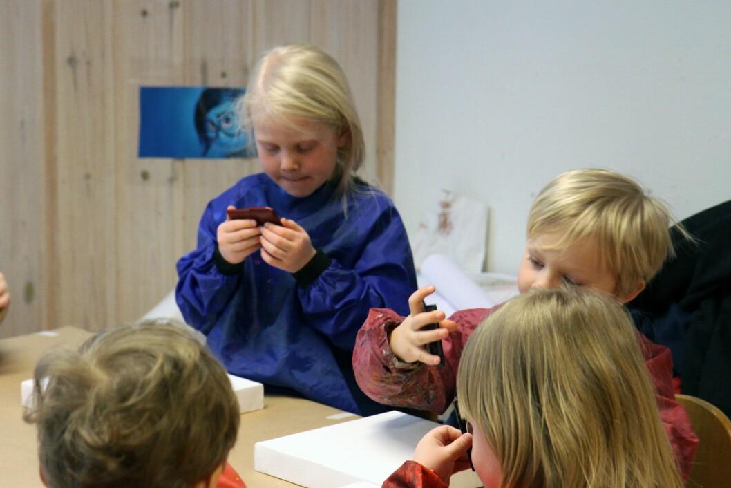 Barna bruker speil som hjelpemiddel når de skal tegne sitt eget ansikt.