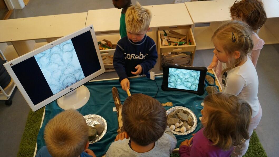 Barna bruker et digitalt mikroskop til å undersøke det de har funnet ved Ilabekken.