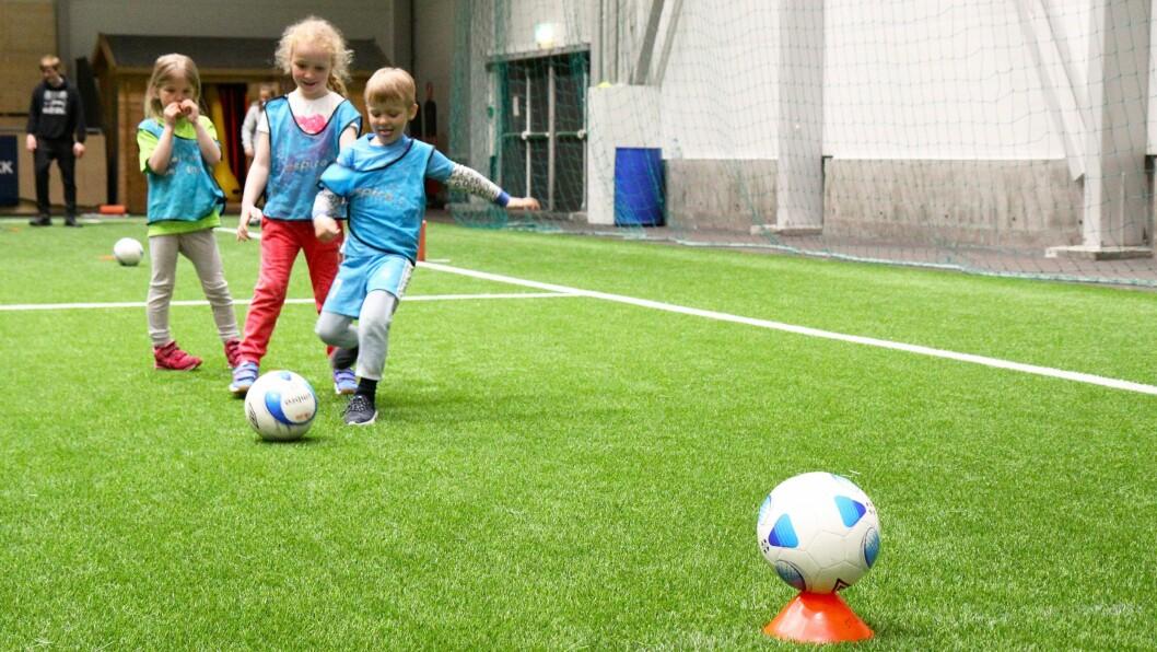 Barna fikk delta i aktiviteter med og uten ball. Her skal de prøve å treffe en fotball med en annen fotball. Foto: Silje Wiken Sandgrind
