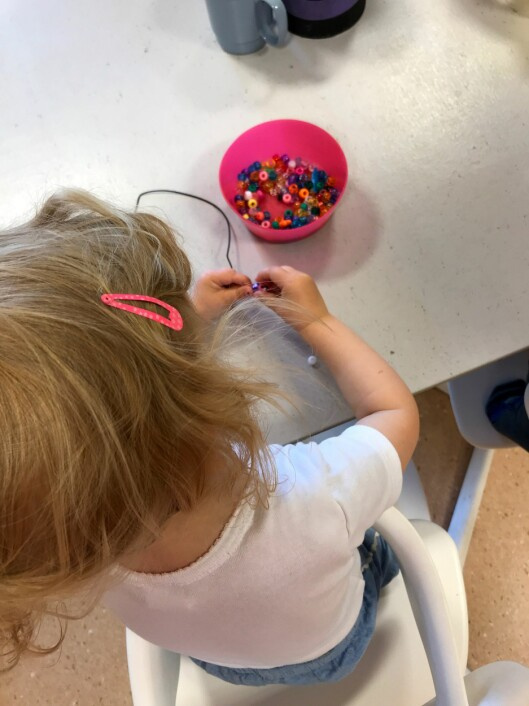 Her er en av barna fra barnehagen i gang med å perle et armbånd til festen.