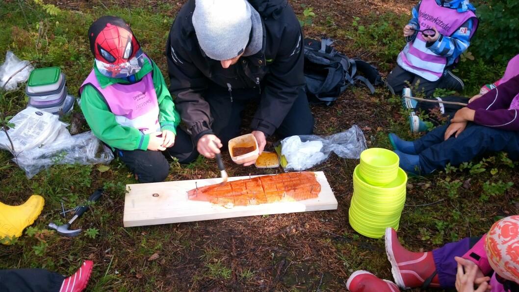 Barna og pedagogisk leder Alexander Kringstad Aanes i Læringsverkstedet Hammersborg barnehage tilbereder laks som skal stekes på bålet.
