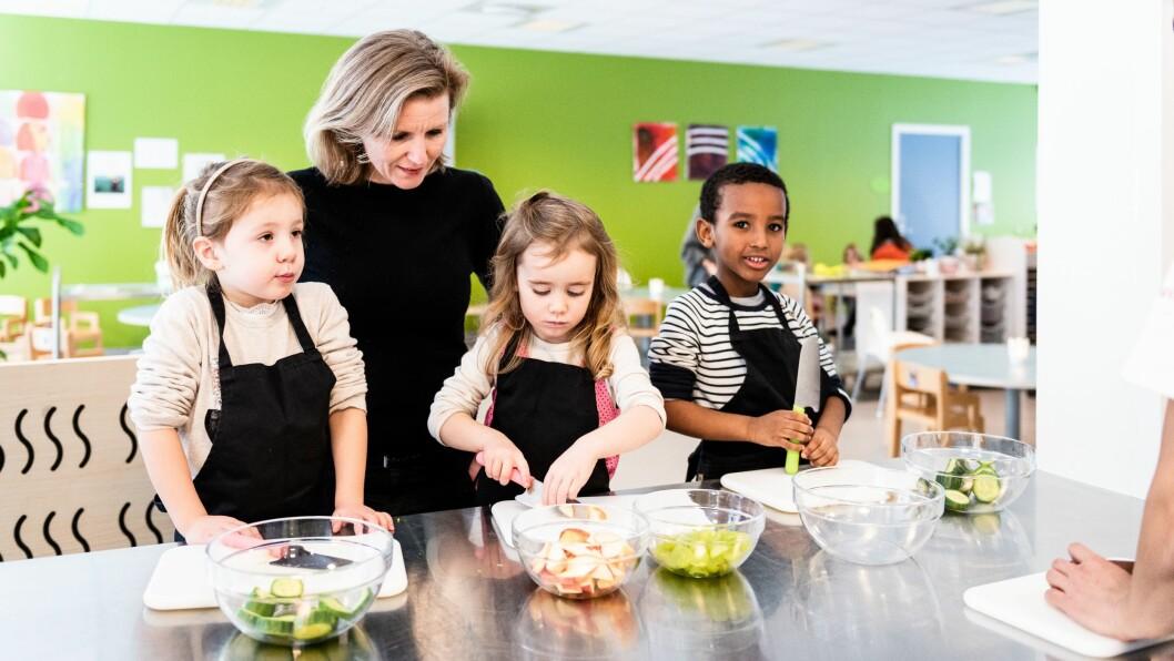 Sofie, Astrid og Abudullahi lager lunsj med forbrukerrådets Anne Kristin Vie på barnehagen Espira Grefsen stasjon barnehage.