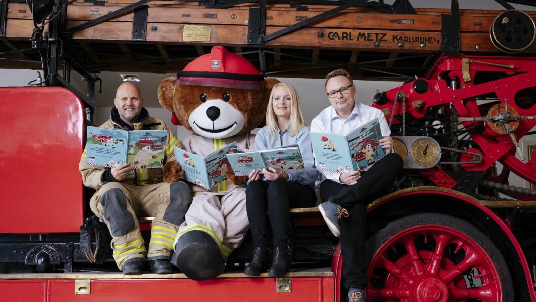 – For oss er barnebøker en helt ny måte å formidle viktig brannvernkunnskap på, sier Håvard Kleppe i Brannvernforeningen. Her sitter han til høyre for, Rikard Heimen. Bjørnis og Marthe Gravseth Aspen.