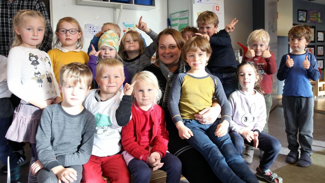Pedagogisk leder Lene Lysell sammen med skolestartere i Huseby barnehage.