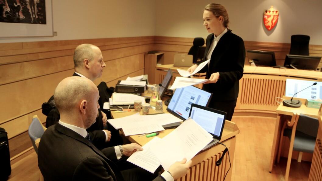 Advokatfullmektig Hanne Inger Bjurstrøm Jahren fra Regjeringsadvokaten deler ut sakspapirer til motparten. Til venstre partshjelper for Gnist Trøa, advokat Einar Brunes fra PBL.