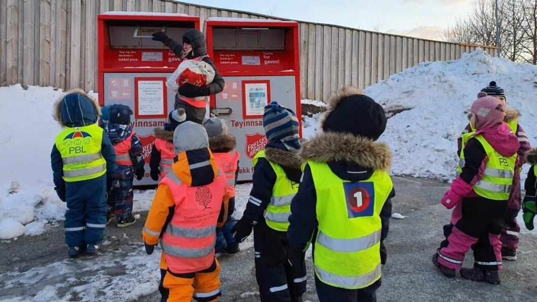 Barn og voksne leverer overskuddklær etter byttedagen til Fretex.