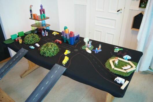Bordplaten er en god flate å bygge på. Brei ut og teip fast et gråpapir, eller en papirduk og tegn veier, parkeringsplasser og parker.