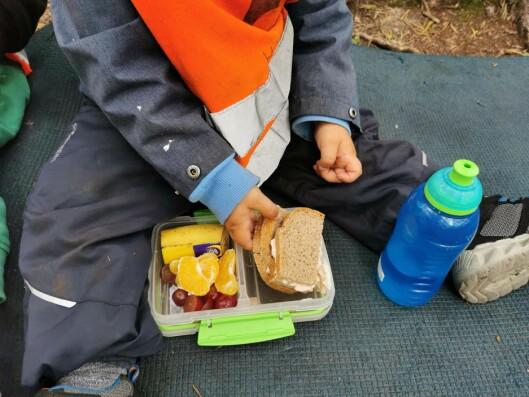 Ungene er spente når de åpner matpakkene hjemmefra.