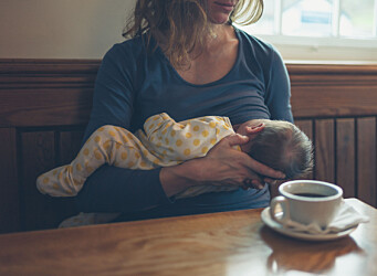 A young mother is breastfeeding her baby in a cafe while she is having a coffee