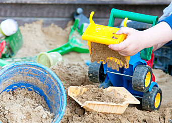 child playing in a sandbox on the playground
