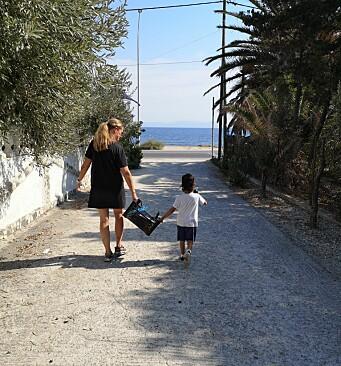"""<span class="""" italic"""" data-lab-italic_desktop=""""italic"""">Marit Heldal og et av barnehagebarna bærer utstyr ned til stranda hvor barna i Mikros Dounias får vanntilvenning og svømmeopplæring av spanske livvakter.</span>"""